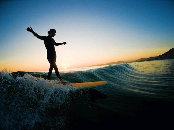 woman longboarding sunset silhouette