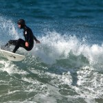 Male surfer in black wetsuit and hood making a turn