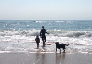 father daughter and dog surfing