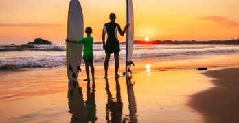 father and son surfers sunset